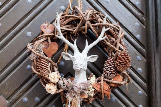Decorative christmas season wrath with a deer on a brown door