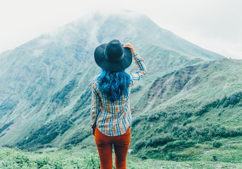 Woman looking at mountains, rear view.