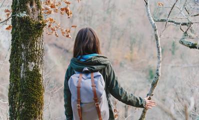 Female hiker walking in autumn forest.