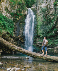 Explorer man looking at waterfall.