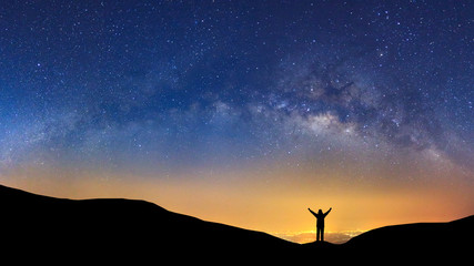 Panorama landscape with milky way, Night sky with stars and silhouette of a standing sporty man with raised up arms on high mountain.