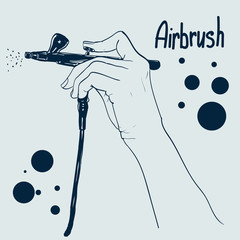 Hand holding a professional airbrush.