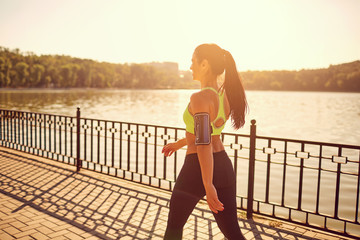 A sporty girl is walking in a sporting walk in the park by the lake. Wall mural