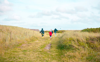Kids children running between dunes in danish Denmark North Sea near blåvand