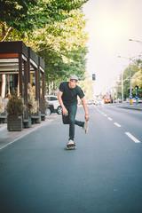Pro skateboarder ride skateboard on capital road street through traffic