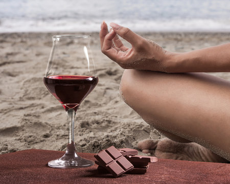 Red wine glass with chocolate and woman practicing yoga on the beach