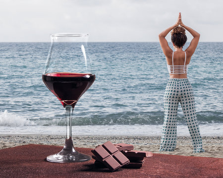 Red wine glass with chocolate and woman practicing yoga near the sea