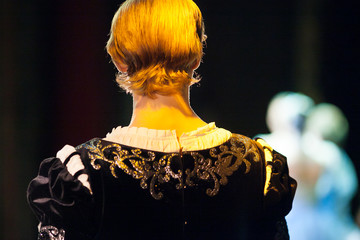 performance, illumination, theater concept. back of the head of man in gorgeous costume of prince, in light of projector his blond hair becomming rich gold shades