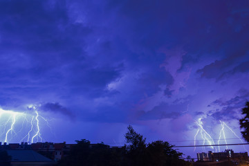 Storm clouds with lightning strike bolts passing over night city of Bangkok cityscape.
