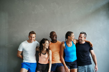 Diverse group of laughing friends standing together at the gym Wall mural
