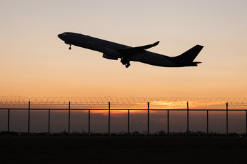 Silhouette takeoff plane from the airport while sunset
