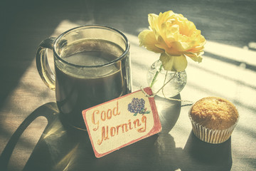 """Retro still life: cup of coffee with label """"Good Morning"""" - photo with vintage color toning."""