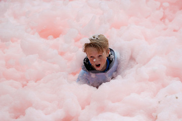A boy falls during a charity bubble run in Leicester