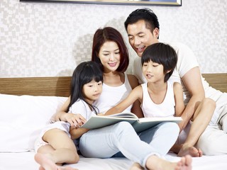 asian family with two children reading book in bedroom