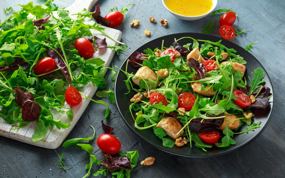 Fresh salad with chicken breast, arugula, nuts and tomatoes on black plate in a wooden table.