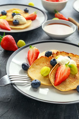 Homemade Pancakes with Blueberry, Strawberry, green Grape and honey syrup. served on plate