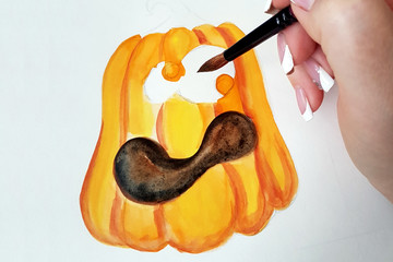 The process of drawing a pumpkin with watercolor on white paper.