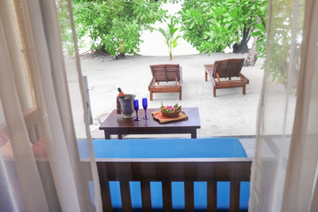 Terrace prepared for romantic date at tropical resort, view through window