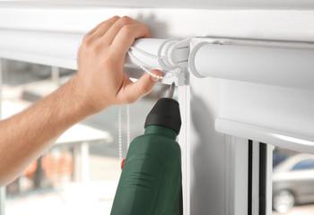 Young man installing window screens indoors