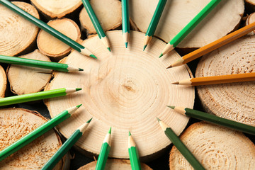 Pencils of green shades on wooden stumps