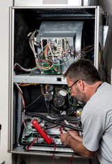 Master technician works on a home furnace with volt meter