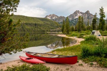 Small red boats along and Idaho lake with tent and mountain Wall mural