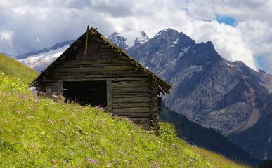 Old cabin in Dolomites with Marmolada peak on the background, Italy