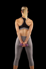 Rear view of sporty woman with perfect buttocks holding dumbbells while standing
