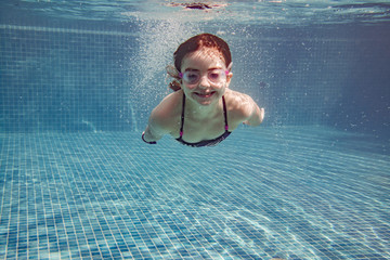 Little girl diving in a pool