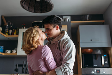 Young family, love and people concept - close up of happy couple hugging on kitchen