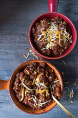 two colorful bowls of chilli with chedder cheese top view closeup