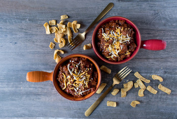 two colorful bowls of chilli with chedder cheese top view