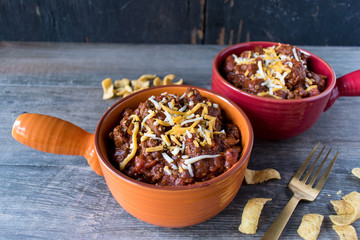 two colorful bowls of chilli with chedder cheese closeup