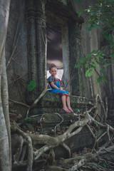 Little girl sitting in a old window