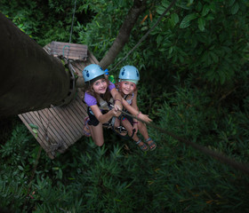 Two little girls rappelling from a tree