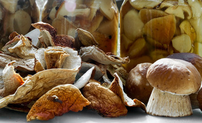 Mushrooms, jam, dried mushrooms and boletus pickled in a jar on  table.