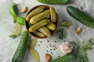 Composition with pickled and fresh cucumbers on gray textured background
