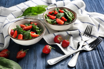 Bowls with strawberry spinach salad on table