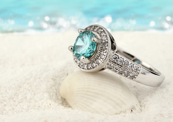 Jewelry ring with clean aquamarine gem on sand beach background