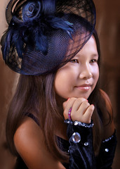 Portrait of Japanese teenage girl with a black hat on a hair clip with mesh and feathers