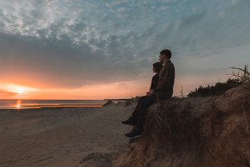 young loving couple enjoying the sunset on the sea in autumn.