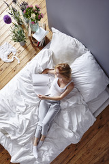 young red haired woman relaxing in bed reading magazine fresh scandinavian atmosphere