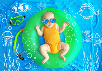 Cute baby with swimming ring and snorkeling mask lying on blue bedspread. Holidays at sea with baby, concept