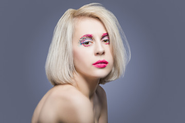 Beauty and fashion Ideas. Portrait of Caucasian Blond Female With Vivid Artistic Facial Makeup Against Gray.