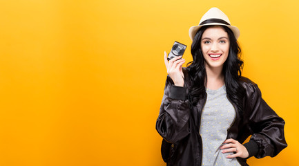 Young woman holding a compact camera on a solid background