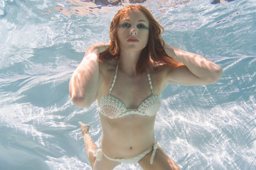 Woman with red hair in a swimming pool.