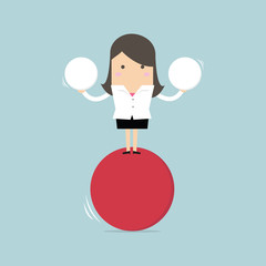 Businesswoman balancing on red ball holding two spheres.