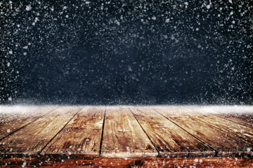 Wall Mural - Christmas and New year background with wooden deck table and snowfall. Empty display for product montage. Rustic vintage Xmas background.