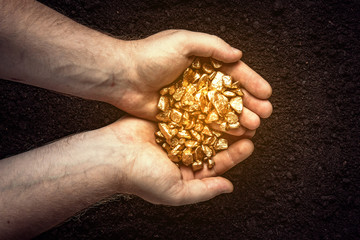 Gold nuggets the hands of the miner.  The working hands of a peasant with pure gold. top view Fototapete