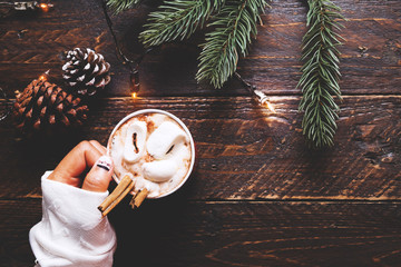 Christmas background - Girl hand holding cup of hot chocolate on wood table with rustic decoration and copy space, flat lay, top view. vintage color tone style.